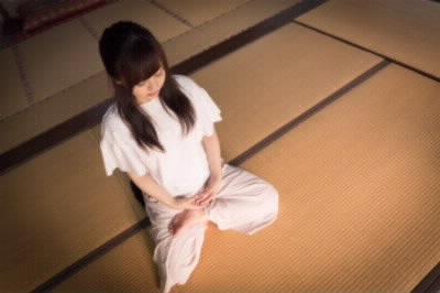 半跏趺坐(はんかふざ)で座る女性